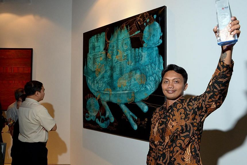 Indonesian artist Antonius Subiyanto with his acrylic painting Old Stock Fresh Menu, which bagged the UOB South-east Asian Painting of the Year Award, worth US$10,000. -- ST PHOTO: DESMOND WEE