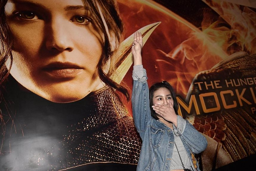 A Thai student flashes a three-finger salute, an unofficial symbol of resistance against the army's May coup, as she stands by a poster of the latest Hunger Games film, at a cinema hall in Bangkok on Nov 20, 2014. -- PHOTO: AFP
