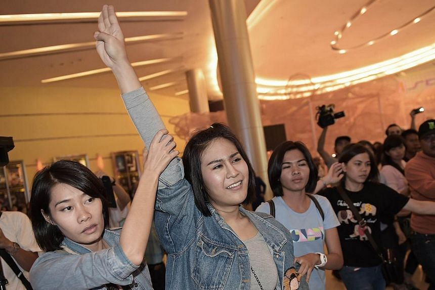 A Thai student (centre) flashes a three-finger salute, an unofficial symbol of resistance against the army's May coup, as she is escorted out of a cinema hall by plainclothes female police officers in Bangkok on Nov 20, 2014. -- PHOTO: AFP