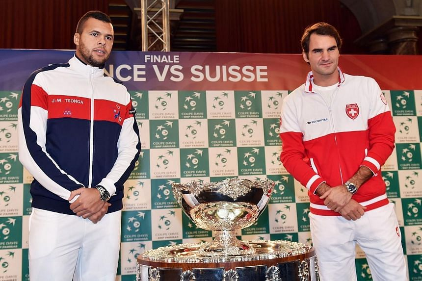 Swiss Davis Cup team player Roger Federer (right) poses with French Davis Cup team player Jo-Wilfried Tsonga next to the Davis Cup trophy after the draw of the Davis Cup final France vs Switzerland on Nov 20, 2014, in Lille. Switzerland's tennis