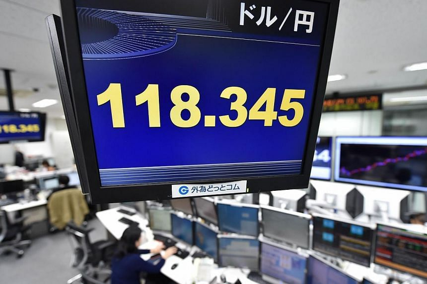 A foreign exchange rate board (upper) is displayed at a foreign exchange brokerage in Tokyo on Nov 20, 2014.The Japanese currency is sinking. -- PHOTO: AFP