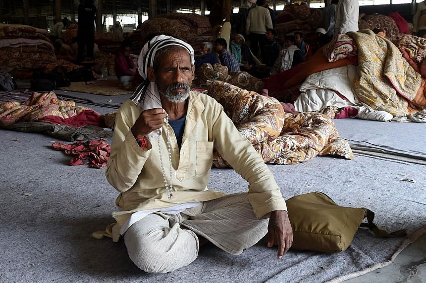 A follower of self-styled 'godman' Rampal Maharaj uses prayer beads as he looks on in the ashram hall at Barwala in the district of Hisar, some 175 kilometres north of New Delhi on Nov 20, 2014.From sex scandals to bloody sieges, India's many s