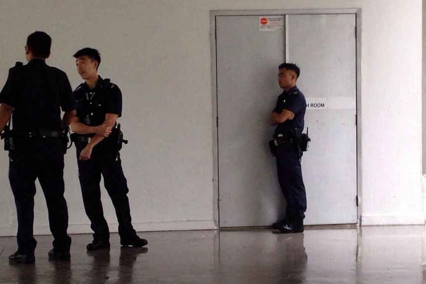 Police officers standing outside the switch room at the foot of the HDB block in Ang Mo Kio. -- PHOTO: KUA CHEE SIONG