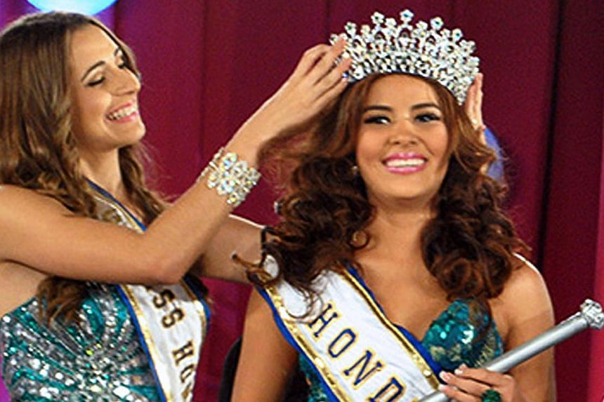 An undated picture taken in San Pedro Sula of Maria Jose Alvarado (right) as she is crowned Miss Honduras World. Shewas fatally shot as she tried to escape her sister's jealous boyfriend. -- PHOTO: AFP