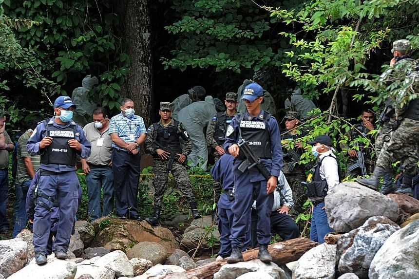 Forensic experts and soldiers work where the bodies of Miss Honduras Maria Jose Alvarado and her sister Sofia Trinidad were found, near Aguagua river in Santa Barbara, 200km north-east of Tegucigalpa, Honduras on Nov 19, 2014. -- PHOTO: AFP