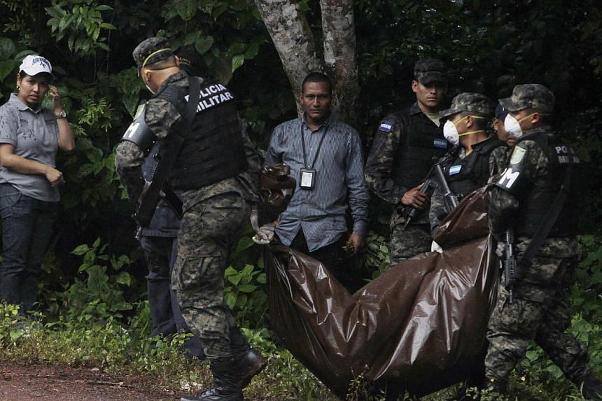 Soldiers carry a body bag near a crime scene in Arada on Nov 19, 2014. The bodies of Maria Jose Alvarado, 19, and her sister Sofia, 23, were found buried near a river in the mountainous region of Santa Barbara in western Honduras. -- PHOTO: REUTERS