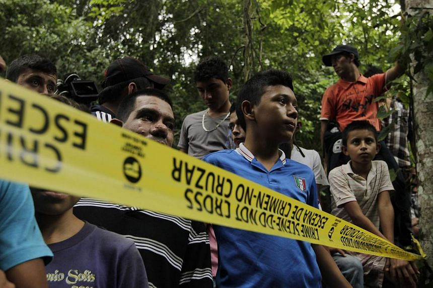 Onlookers stand behind a yellow police tape near a crime scene where Maria Jose and Sofia Alvarado's dead bodies were found in Arada on Nov 19, 2014. -- PHOTO: REUTERS