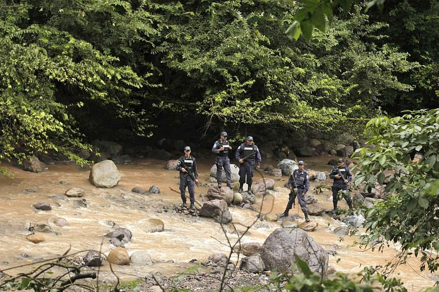 Police officers stand guard near a crime scene in Arada on Nov 19, 2014. The bodies of Maria Jose Alvarado, 19, and her sister Sofia, 23, were found buried near a river in the mountainous region of Santa Barbara in western Honduras. -- PHOTO: REUTERS