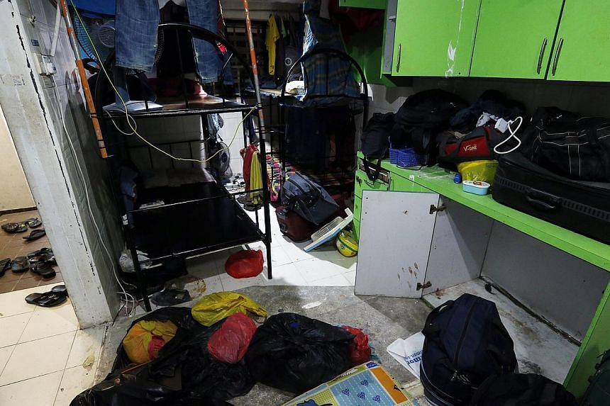In two condo units in Selegie Centre, about 50 workers live out of their luggage amid damp and soiled clothes, and sleep on grimy floors without mattresses or in bunk beds crammed together.