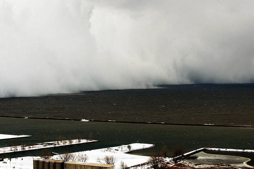 A Lake Effect snow storm with freezing temperatures produces a wall of snow travelling over Lake Erie into Buffalo, New York on Nov 18, 2014. -- PHOTO: REUTERS