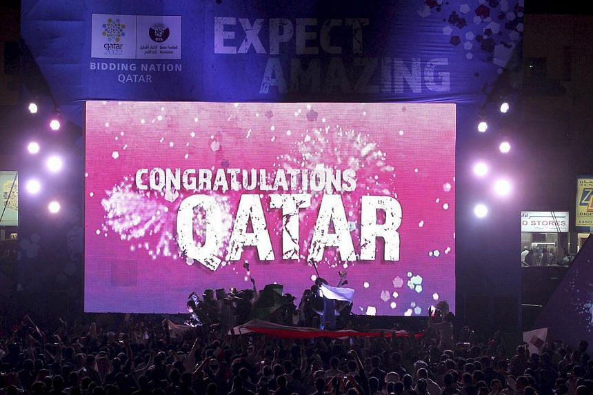 """People celebrate in front of a screen that reads """"Congratulations Qatar"""" after Fifa announced that Qatar will be host of the 2022 World Cup in Souq Waqif in Doha on Dec 2, 2010. Ms Phaedra Almajid, a whistleblower who gave evidence of corruption agai"""