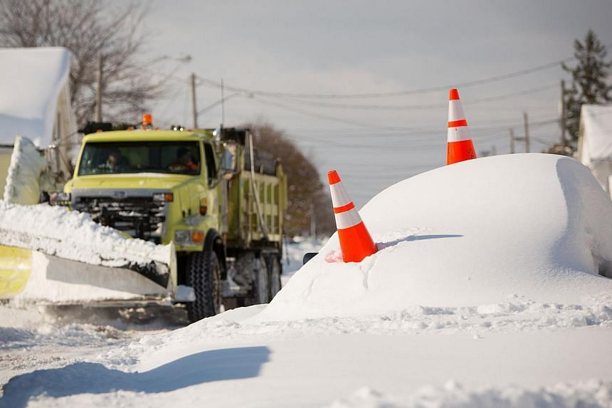 An abandon car marked by orange cones is buried under snow as a snowplow passes by in Buffalo, New York, on Nov 19, 2014. Western New York state braced for a fresh wave of heavy snow after a freakish storm swept off the Great Lakes and deposited as m
