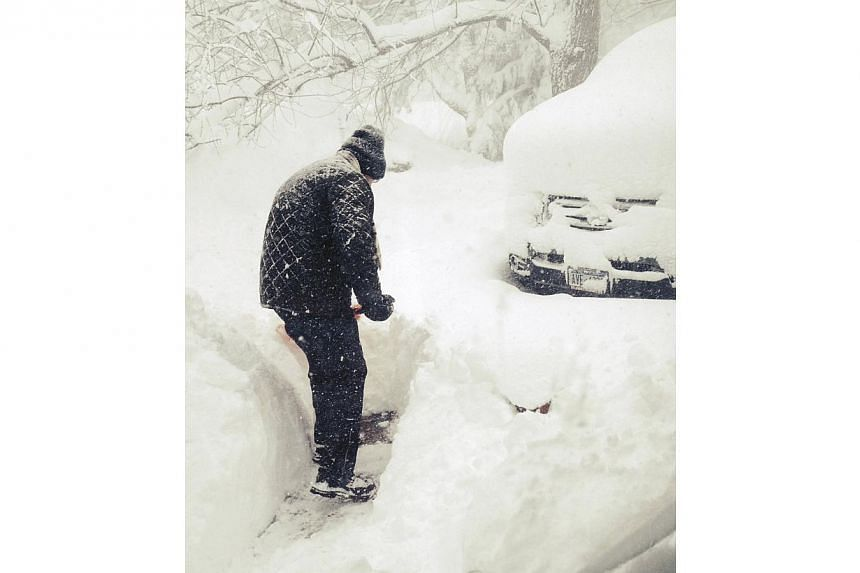 Mr Steven Gros shovels snow from outside his home in Orchard Park, New York, on Nov 18, 2014. -- PHOTO: REUTERS