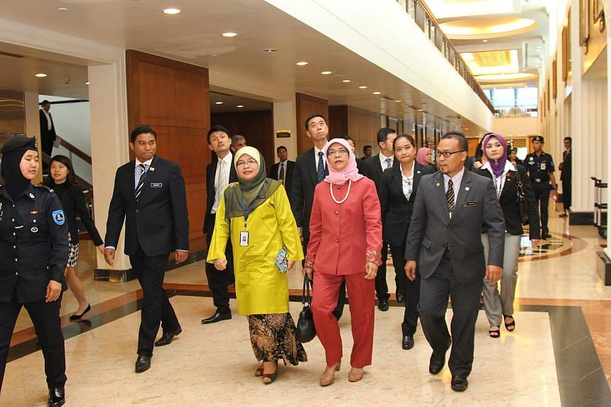 Madam Halimah (in red) flanked by Malaysian officials in a corridor of the Malaysian Parliament in Kuala Lumpur, on Wednesday. -- PHOTO: SINGAPORE PARLIAMENT HOUSE