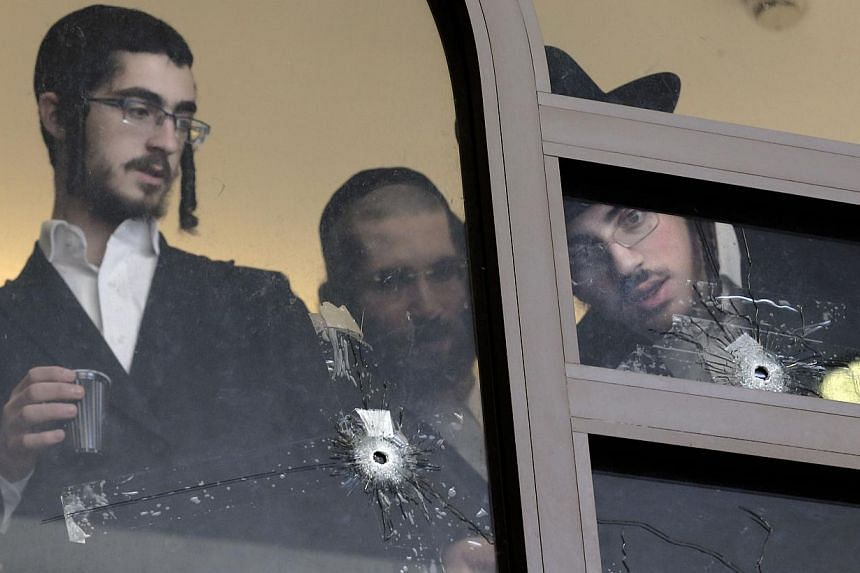 Ultra Orthodox Jews look on Nov 19, 2014 at bullet holes in the main window of a synagogue in Jerusalem which was attacked the previous day by two Palestinians armed with a gun and meat cleavers, leaving five Israeli worshipers killed. The UN Securit