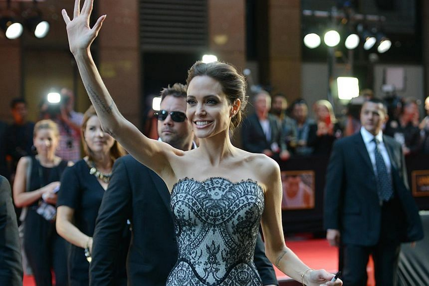 This file photo taken on November 17, 2014 shows US actress and director Angelina Jolie waving to fans as she arrives for the world premiere of her new movie Unbroken in Sydney. -- PHOTO: AFP