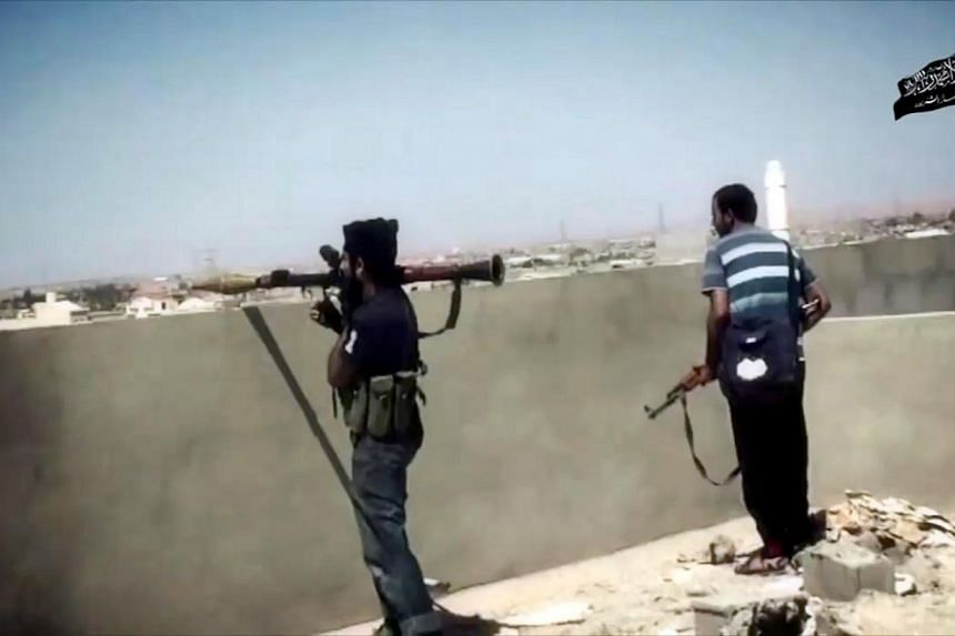 An image taken from a video made available on Oct 9, 2014, allegedly shows Ansar al-Sharia militants during a battle in the Libyan city of Benghazi, the country's second biggest city. -- PHOTO: AFP