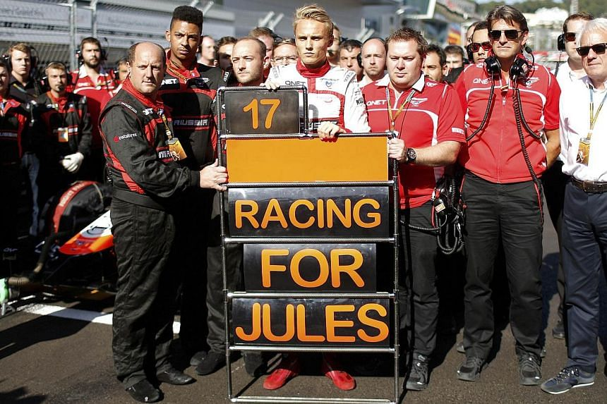 Marussia Formula One driver Max Chilton (centre) and his team members pray for driver Jules Bianchi who had accident in the previous race, before the first Russian Grand Prix in Sochi on Oct 12, 2014. The Marussia Formula One team has failed in a lat