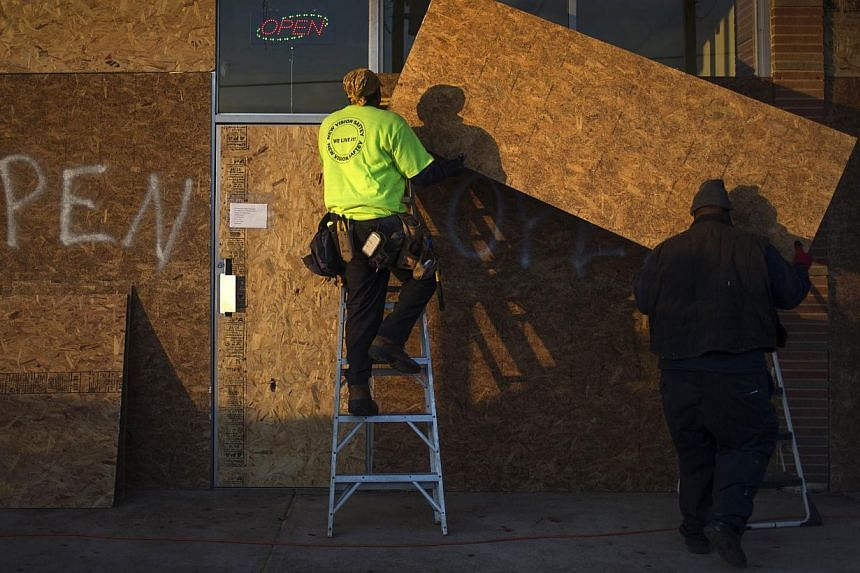 Workers board up businesses in preparation for the grand jury verdict in the shooting death of Michael Brown in Ferguson, Missouri on Nov 19, 2014. -- PHOTO: REUTERS