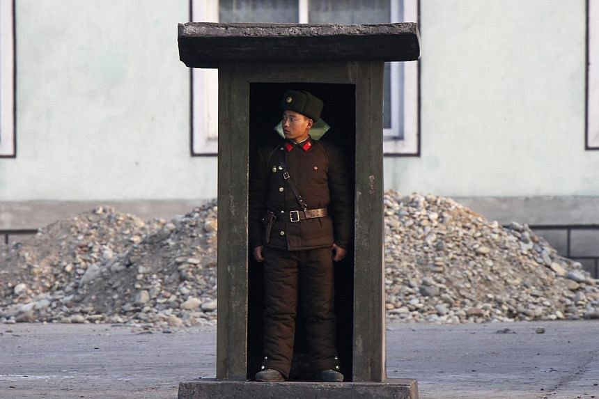 A soldier stands guard at a sentry on the banks of the Yalu River, near the North Korean town of Sinuiju, opposite the Chinese border city of Dandong, on Nov 15, 2014. New satellite imagery suggests North Korea may be firing up a facility for process