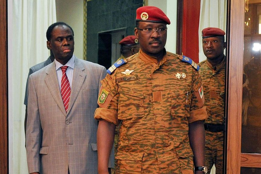 Burkina interim President Michel Kafando (left) walks with Lieutenant-Colonel Isaac Zida (right) on Nov 19, 2014 at the presidential palace in Ouagadougou. Zida, who took power after the fall of Burkina Faso President Blaise Compaore, was named on No