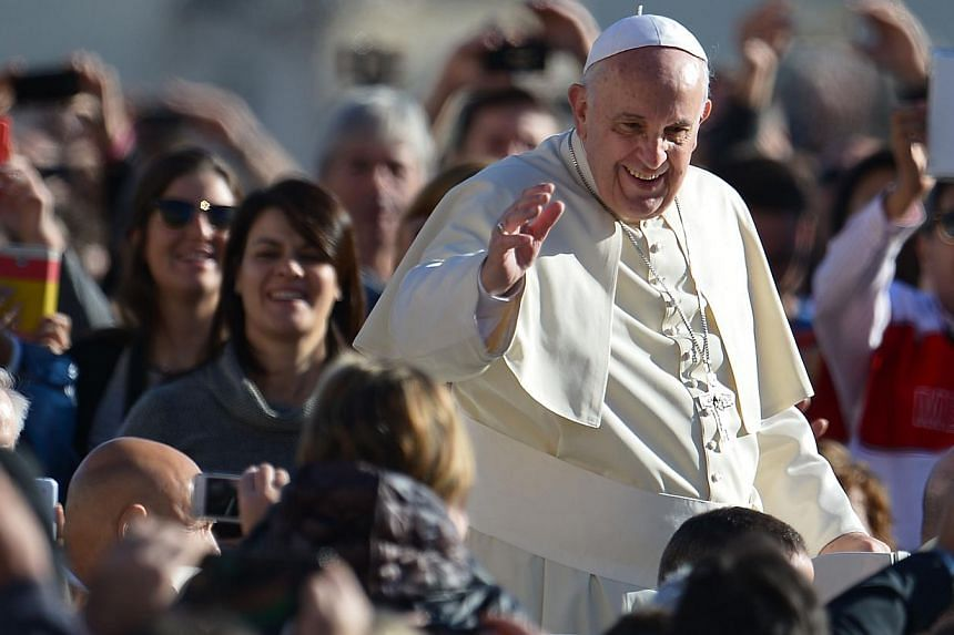 Pope Francis greets the crowd as he arrives for his general audience at St Peter's square on November 19, 2014 at the Vatican. Pope Francis is raffling off unwanted gifts including a Fiat Panda, tandem bike and coffee machine to raise money for the h