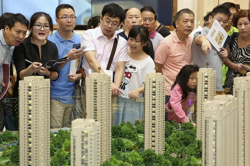 Customers look at a model of a new residential compound at a showroom of Longfor Properties, in Hangzhou, Zhejiang province, in this Aug 17, 2014 file picture. Credit rating agency Standard and Poor's said on Wednesday that China's over-priced a
