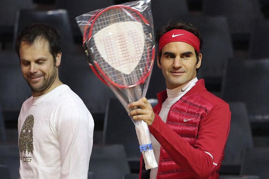 Roger Federer of Switzerland (right) waves as he arrives with Swiss captain Severin Luthi during a Davis Cup tennis training session at the Pierre Mauroy stadium in Villeneuve d'Ascq, northern France, Nov 19, 2014. France will face Switzerland in the