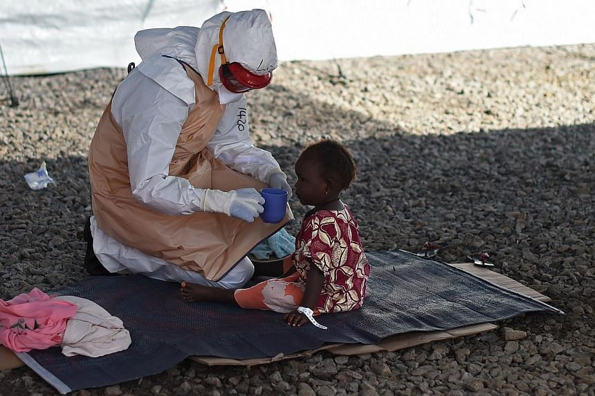 A health worker wearing protective equipment gives a drink to a young Ebola patient at Kenama treatment centre run by the Red Cross Society on Nov 15, 2014.The toll in the Ebola epidemic has risen to 5,420 deaths out of 15,145 cases in eight co