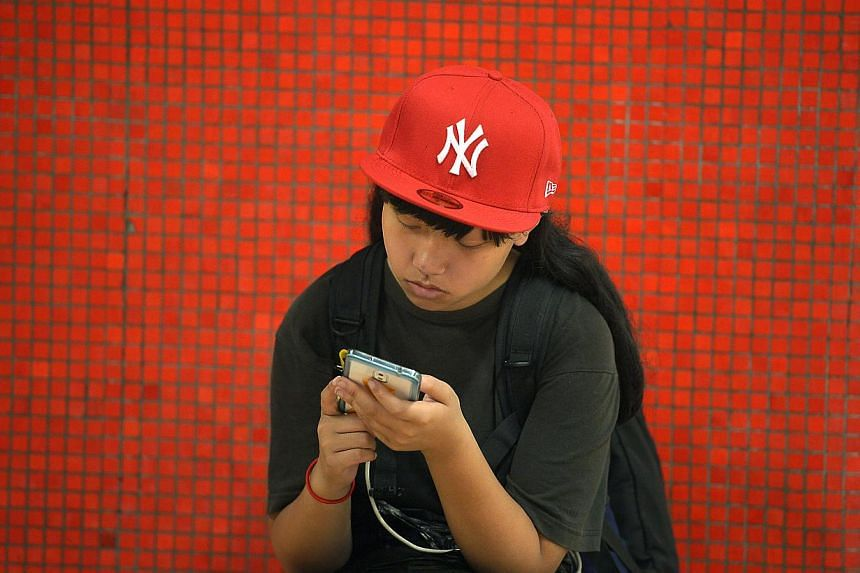 A commuter using her mobile phone at a Sheung Wan train station in Hong Kong. -- PHOTO: ST FILE