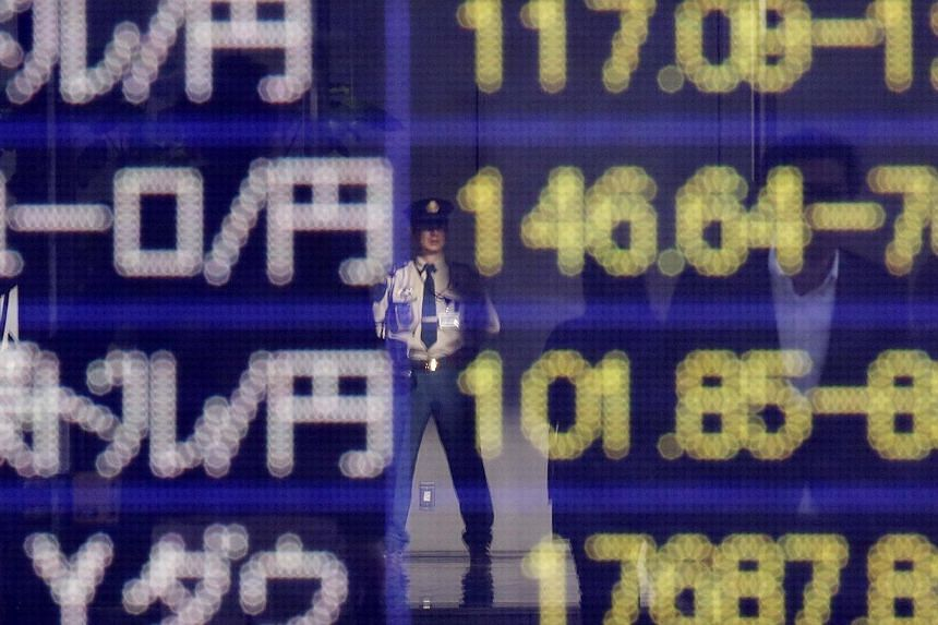 A security worker is reflected in an electronic board showing the exchange rates between the Japanese yen against the US dollar, the euro, and Australian dollar, and market indices of Dow Jones, outside a brokerage in Tokyo, on Nov 19, 2014. -- PHOTO