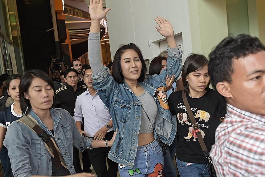 A Thai student (centre) holding her arms up as she is escorted out of a cinema hall by plainclothes police officers in Bangkok on Nov 20, 2014. Political protests are banned under martial law, but that has not stopped some university students from st