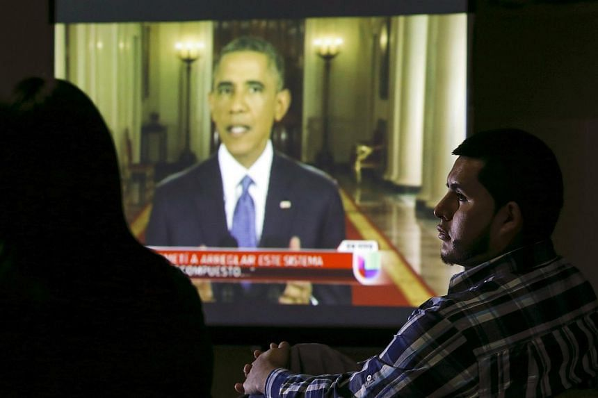 A group of legal and undocumented immigrants watch US President Barack Obama speaking about the country's immigration policy during a nationally televised address from the White House in Washington, on a screen in New Brunswick, New Jersey on Nov 20,