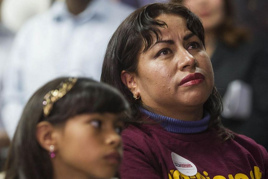 In Los Angeles, California, Nancy Catano, 41, a non-US citizen, and her daughter Michelle, 9, watch US President Barack Obama's nationally televised announcement on immigration reform on Nov 20, 2014. -- PHOTO: AFP