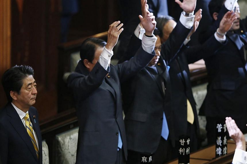 "Japan's Prime Minister Shinzo Abe (2nd left) stands next his cabinet ministers as they raise their hands and shouts ""banzai"" (cheers) after the dissolution of lower house was announced at the Parliament in Tokyo Nov 21, 2014."