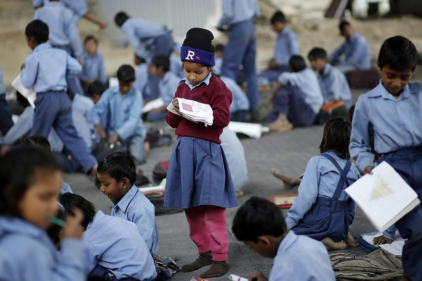 A schoolgirl reads from a textbook at an open-air school in New Delhi on Nov 20, 2014.Indians were flying aeroplanes, carrying out stem cell research and may even have been using cosmic weapons 5,000 years ago, according to the chairman of Indi