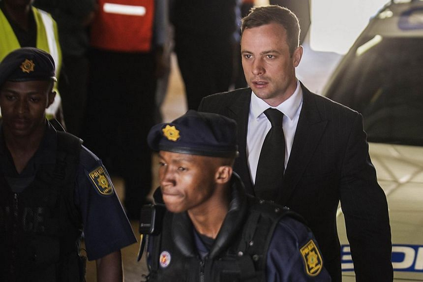 South African Paralympian athlete Oscar Pistorius (centre) is escorted to a police vehicle to be transported to prison following his sentencing at the High Court in Pretoria on Oct 21, 2014.Oscar Pistorius, serving a five-year jail sentence for