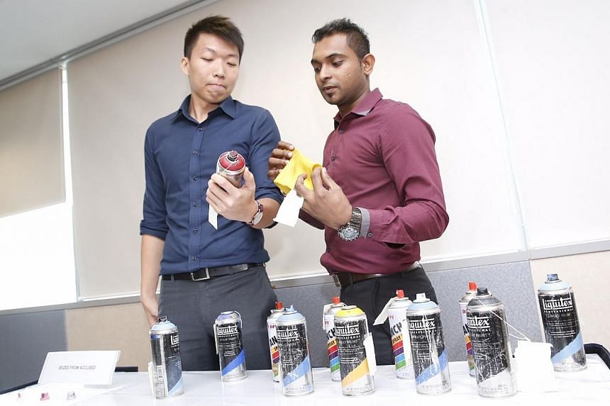 Investigators from Tanglin Police Division with seized items from the vandals at a police conference at Cantonment Complex on Nov 21, 2014. -- ST PHOTO: KEVIN LIM