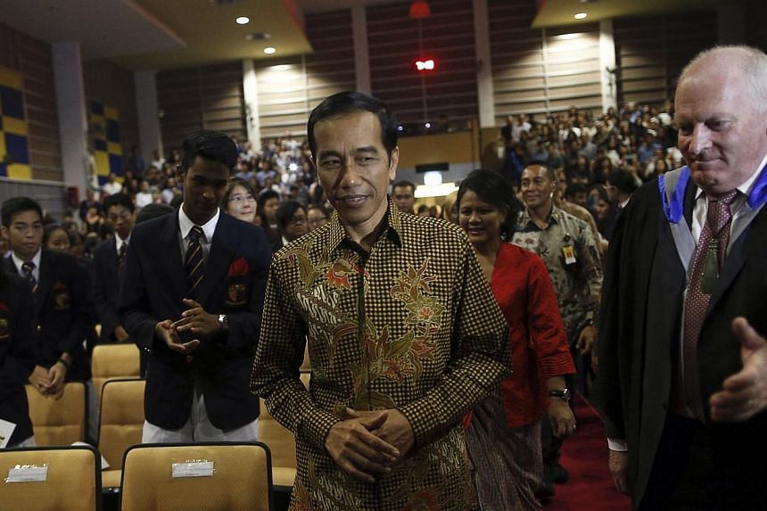 """Indonesian President Joko """"Jokowi"""" Widodo arrives with his wife Iriana to attend their son's graduation ceremony at Anglo-Chinese School (ACS) International in Singaporeon Nov 21, 2014. -- PHOTO: REUTERS"""