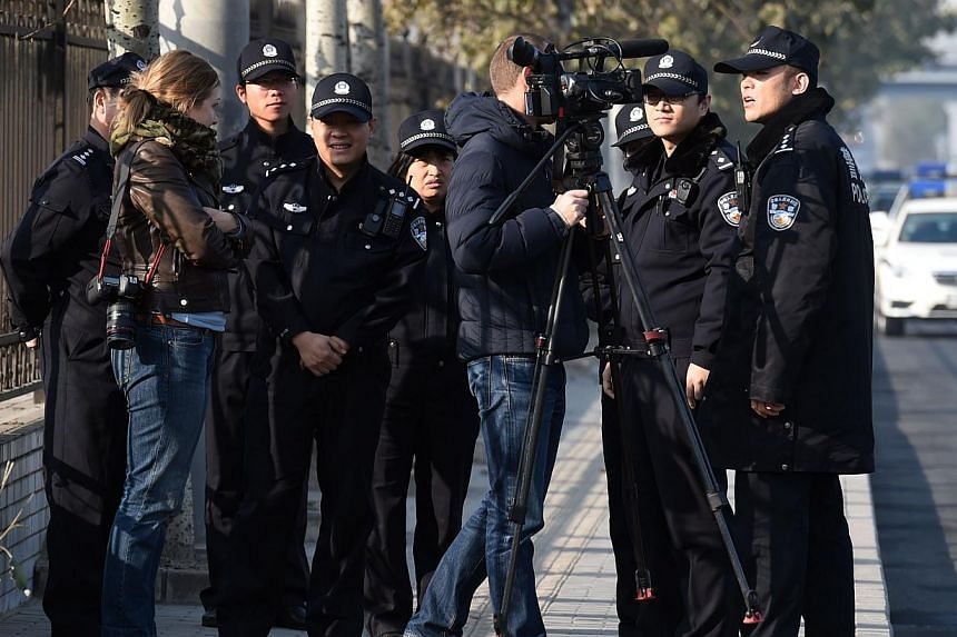 Police order foreign journalists to leave the street opposite the Beijing No. 3 Intermediate People's Court where the trial of veteran former journalist Gao Yu on charges of leaking state secrets takes place in Beijing on Nov 21, 2014.An outspo
