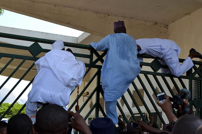 Nigerian parliament members climb the assembly gate closed by security forces in Abuja on Nov 20, 2014. Nigerian police fired teargas inside parliament, apparently trying to block opposition lawmakers, including the speaker of the lower house, from e