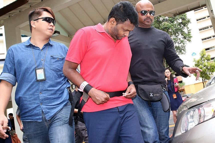 Annadurai Raman (in red) at Block 125 Geylang East Avenue 1 on Nov 18, 2014, where he took part in a crime scene reenactment. Annadurai, the first man to be charged over the brazen robbery of a money changer, has been remanded in prison after failing