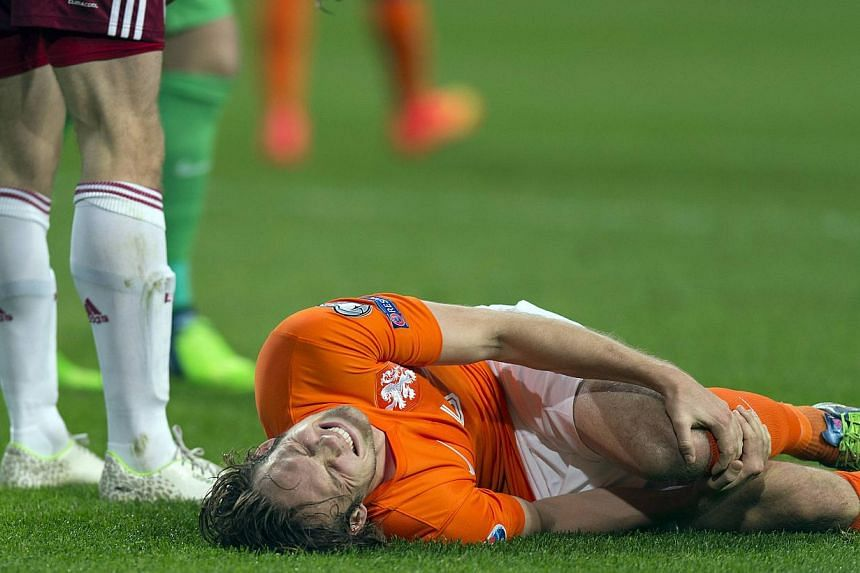 Daley Blind of the Netherlands lies injured after a challenge with Latvia's Eduards Viskanovs during their Euro 2016 Group A qualifying soccer match in Amsterdam Nov 16, 2014. TheManchester United midfielder's knee ligament injury is not as bad