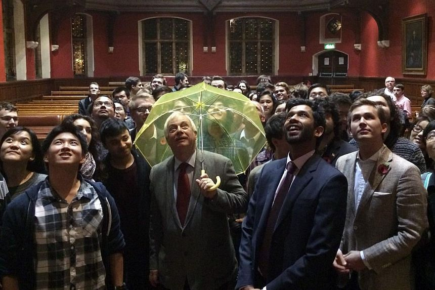 Hong Kong's last British governor, Lord Chris Patten, holding a yellow umbrella - a symbol of the Occupy movement in Hong Kong - given to him by a student in the audience at an Oxford University event. Mr Patten urged nations to stand up to China ove
