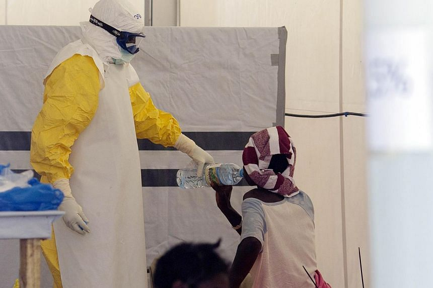 A nurse wearing a personal protective equipment assists a patient at the Ebola treatment centre run by the French Red Cross society in Macenta in Guinea on Nov 20, 2014.US regulators on Thursday suspended trading in four small over-the-counter