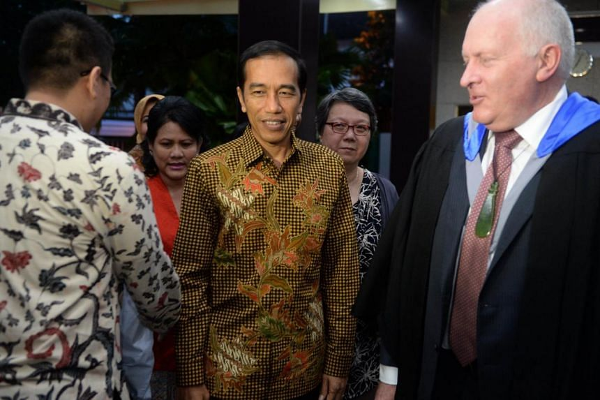 Indonesian President Joko Widodo (centre) and First Lady Iriana arrive for the high school graduation ceremony of their youngest son Kaesang Pangarep at the Anglo-Chinese International School.-- PHOTO: REUTERS