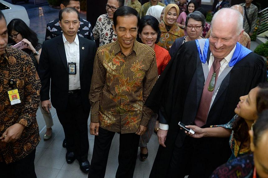 Indonesian President Joko Widodo (centre) and First Lady Iriana (back centre R) arrive for the high school graduation ceremony of their youngest son Kaesang Pangarep at the Anglo-Chinese International School.-- PHOTO: REUTERS