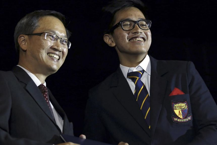 Kaesang Pangarep, son of Indonesian President Joko Widodo, receives his baccalaureate from guest of honour Mountbatten MP Lim Bow Chuanduring his graduation ceremony in Singapore. -- PHOTO: REUTERS