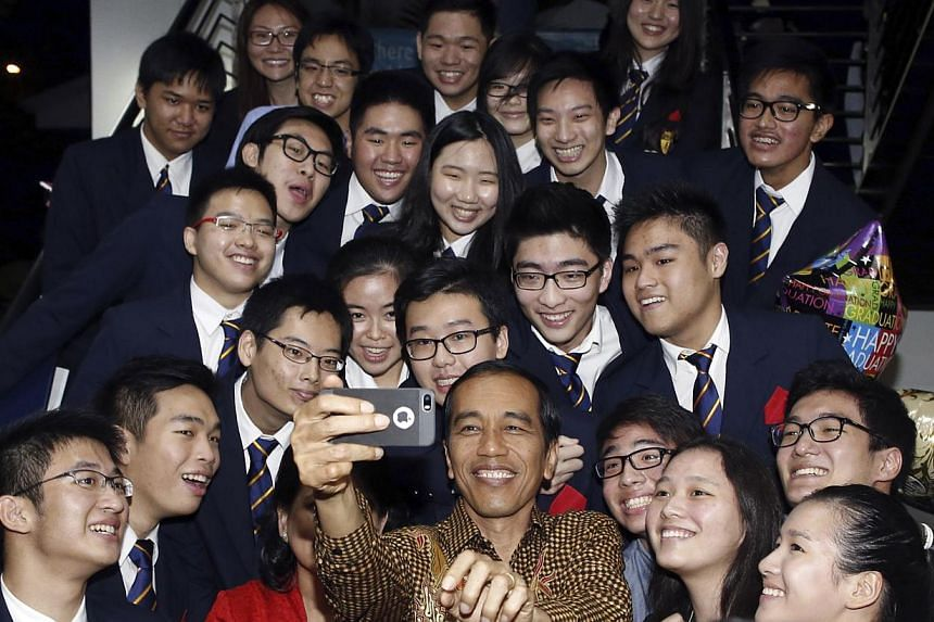 Indonesian President Joko Widodo and his wife Iriana (in red) taking a selfie with their son Kaesang Pangarep (top right) and classmates after his graduation ceremony. -- PHOTO: REUTERS