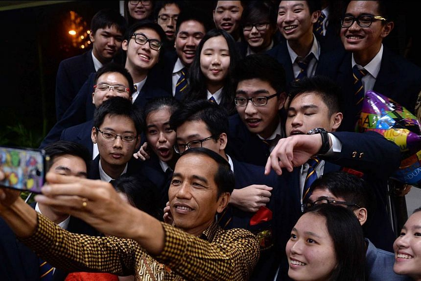 Indonesian President Joko Widodo (front centre) taking a selfie with classmates of his younger son Kaesang Pangarep at the Anglo-Chinese International School in Singapore on Nov 21, 2014. -- PHOTO: AFP